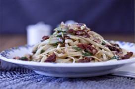 Gluten free spaghetti with sun-dries tomatoes, fresh arugula and pine nuts